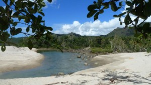 A beautiful scenery with white sands and waters of Ramsay Bay surrounded by hills and trees near Hinchinbrook Island